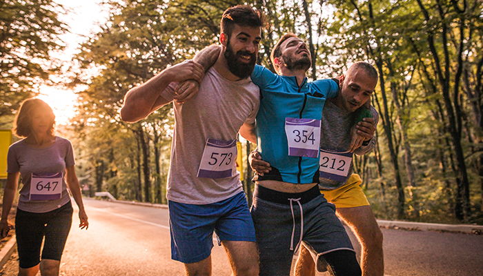 An exhausted runner being helped by two friends