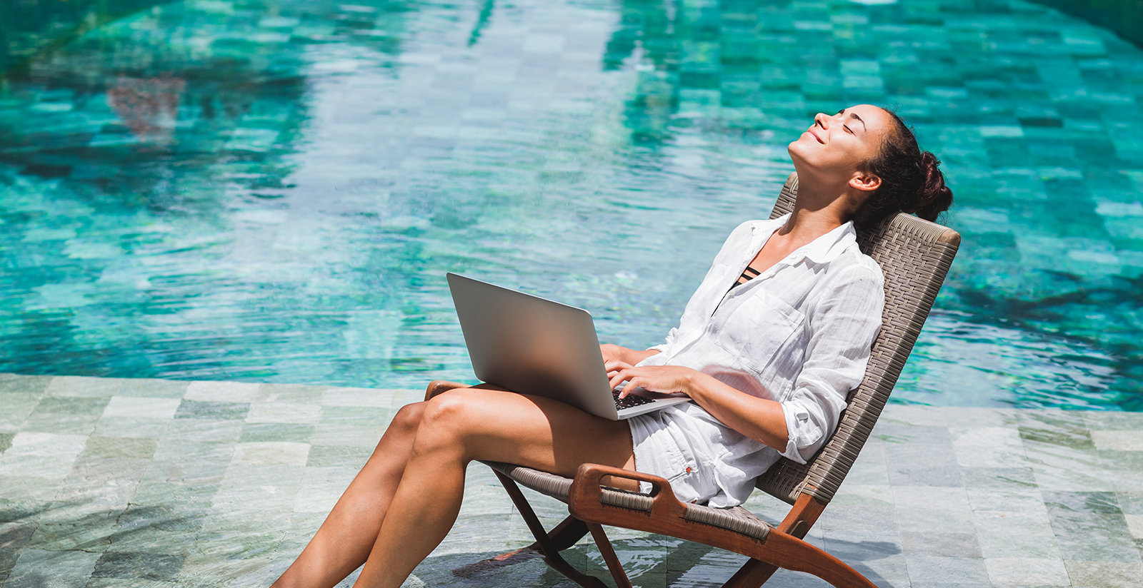 Woman working with laptop by the pool