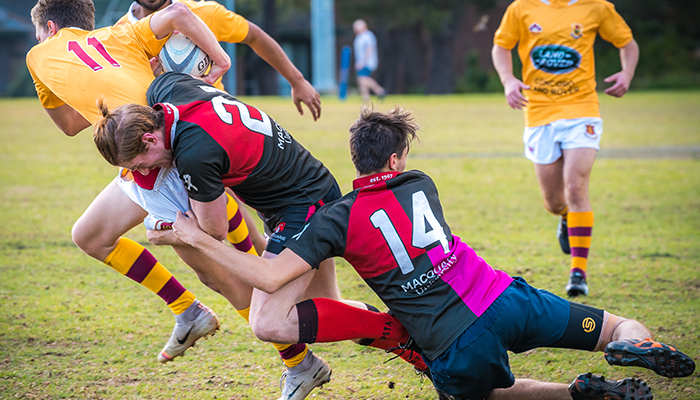 Macquarie University men's rugby players making a tackle